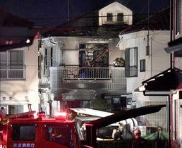 火災のあった住宅(中央)=27日午前4時59分、東京都日野市