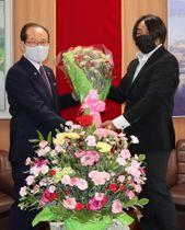 朝長市長にカーネーションを贈呈する山本部会長(右)=佐世保市役所