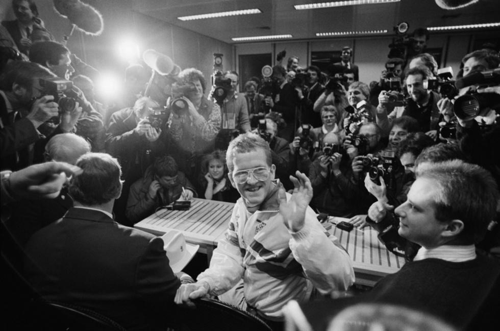 カルガリー冬季五輪からロンドンに戻り、大勢の報道陣に囲まれて空港で記者会見に臨むマイケル・エドワーズ。惨敗にもかかわらず超人気者になり、笑いを振りまいた=1988年3月(ゲッティ=共同)