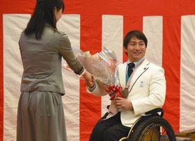 市職員から花束を受け取る森井さん(右)=あきる野市で