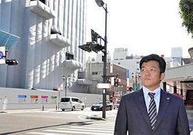 「街がにぎわうきっかけにしたい」と前を向く阿部さん。建設中の建物は福島医大の新学部=28日、福島市本町