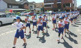 日田川開き観光祭に向け、校区内をパレードする咸宜小の児童ら=21日、日田市中央