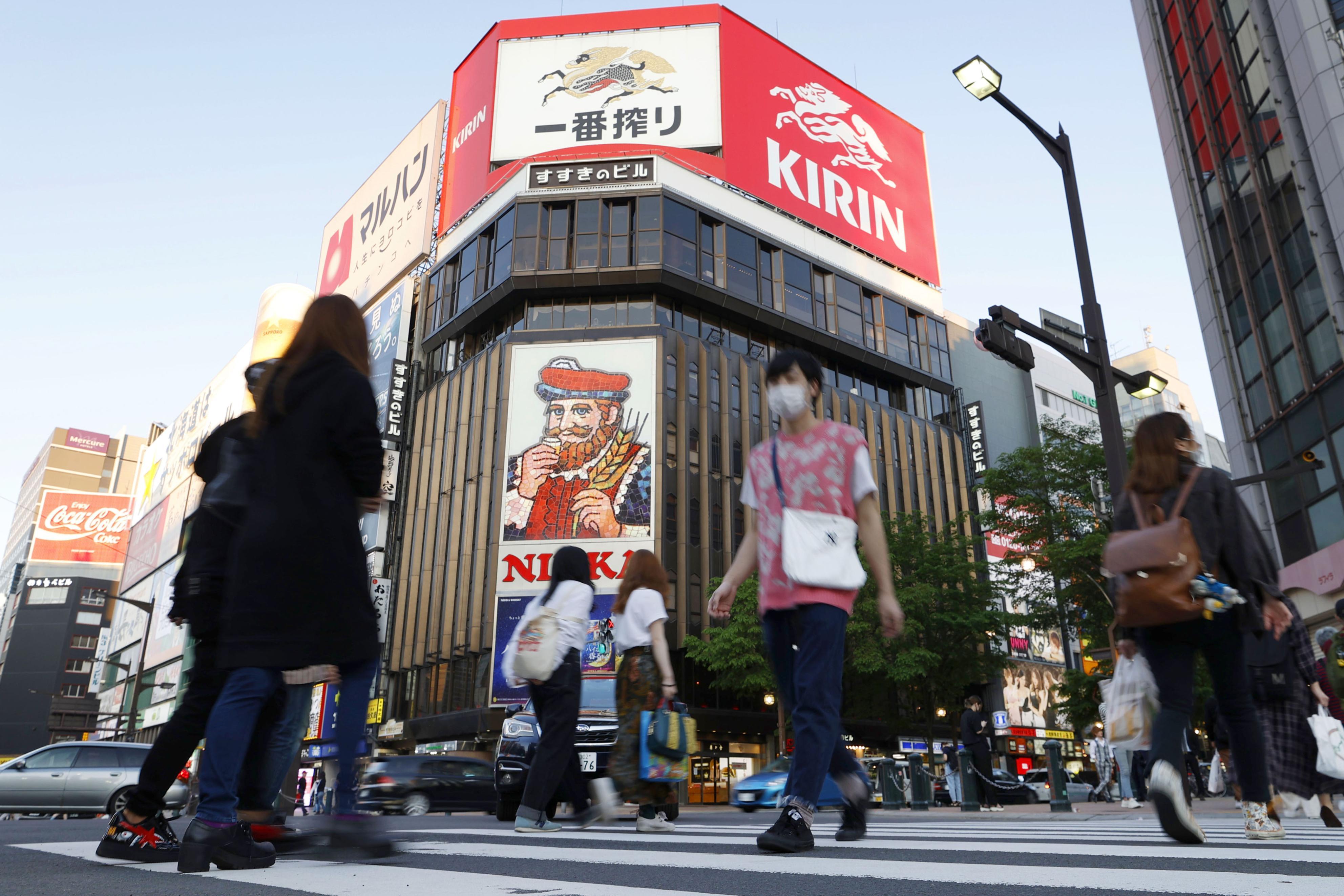 緊急事態宣言が解除されてから最初の週末を迎えた札幌市の繁華街・ススキノを歩く人たち=30日夕