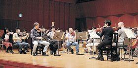 OEK団員と音色を合わせるシュトイデさん(左から3人目)=石川県立音楽堂