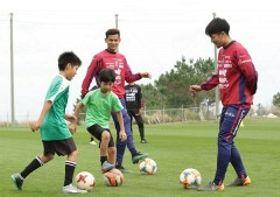 ボールを蹴って子どもと交流するファジアーノ岡山の下口稚葉(右)