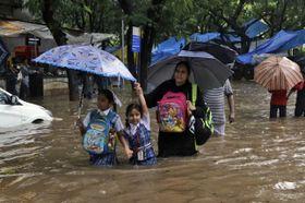 水浸しになった通りを歩く子供たち=8月29日、インド・ムンバイ(AP=共同)