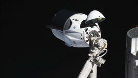 2019年3月の無人飛行で国際宇宙ステーションに近づくクルードラゴン(NASA提供・共同)