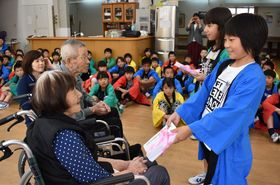 利用者に手紙を手渡す児童たち=長崎市、特別養護老人ホーム喜楽苑