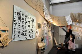 印象に残った塔さんの詩の一節を基に表現された墨アートなどが並ぶ善通寺東、西中合同ボランティアクラブの作品展=善通寺市文京町、市美術館