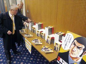 人気漫画「ゴルゴ13」の主人公デューク東郷を活用した安全マニュアルを手に取る企業関係者ら=2017年12月、外務省