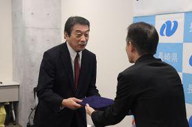 沢水福祉保健部長と協定書を交わす長崎新聞長崎会の松本会長(左)=長崎県庁