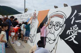 三上剛太郎の壁画を描く佐井小5年生ら=11日、佐井村内