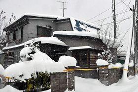 事件から約6カ月、雪が降り積もった青森市旭町1丁目の菊地さんの自宅。窓には破損防止の板がはめられていた=10日午前