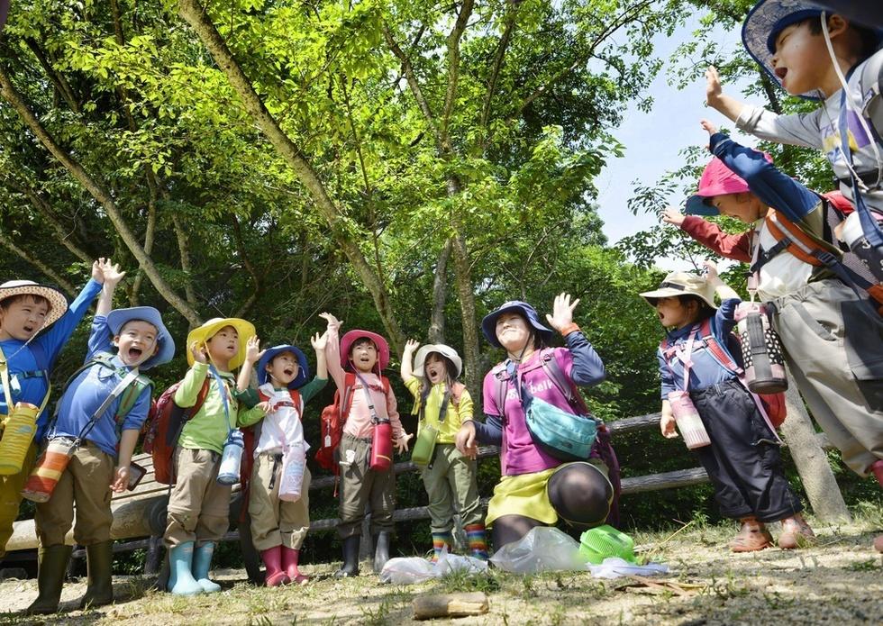 森での一日を振り返る「またねの会」。拝郷弘実が最後に呼び掛ける。「明日も元気に、森のようちえん来れる人!」「ハーイ!」=兵庫県西宮市の甲山森林公園