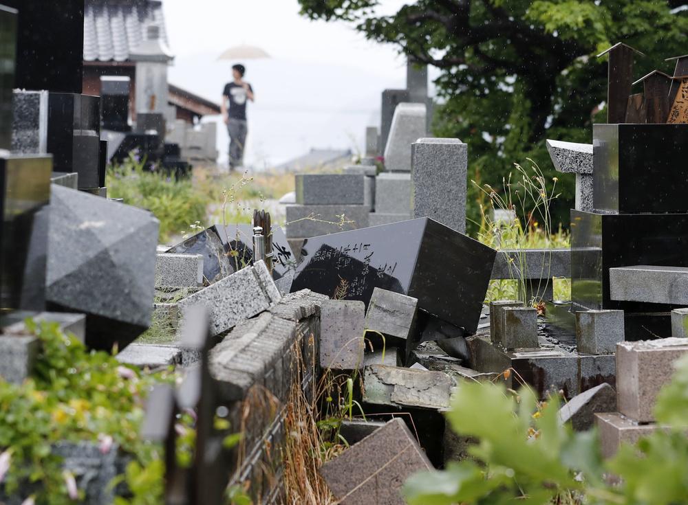 地震で倒壊した墓石=19日午後1時49分、新潟県村上市府屋地区