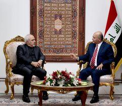 25日、イラクのバグダッドでサレハ大統領(右)と会談するイランのザリフ外相(ロイター=共同)