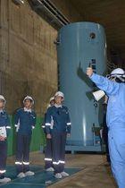 貯蔵区域で施設や模擬キャスク(奥)の説明を受ける山中委員(中)ら=18日午前、むつ市の使用済み核燃料中間貯蔵施設
