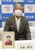 妻まさ子さんの遺影を携えて参加した矢野解光さん=27日午後、熊本県芦北町役場