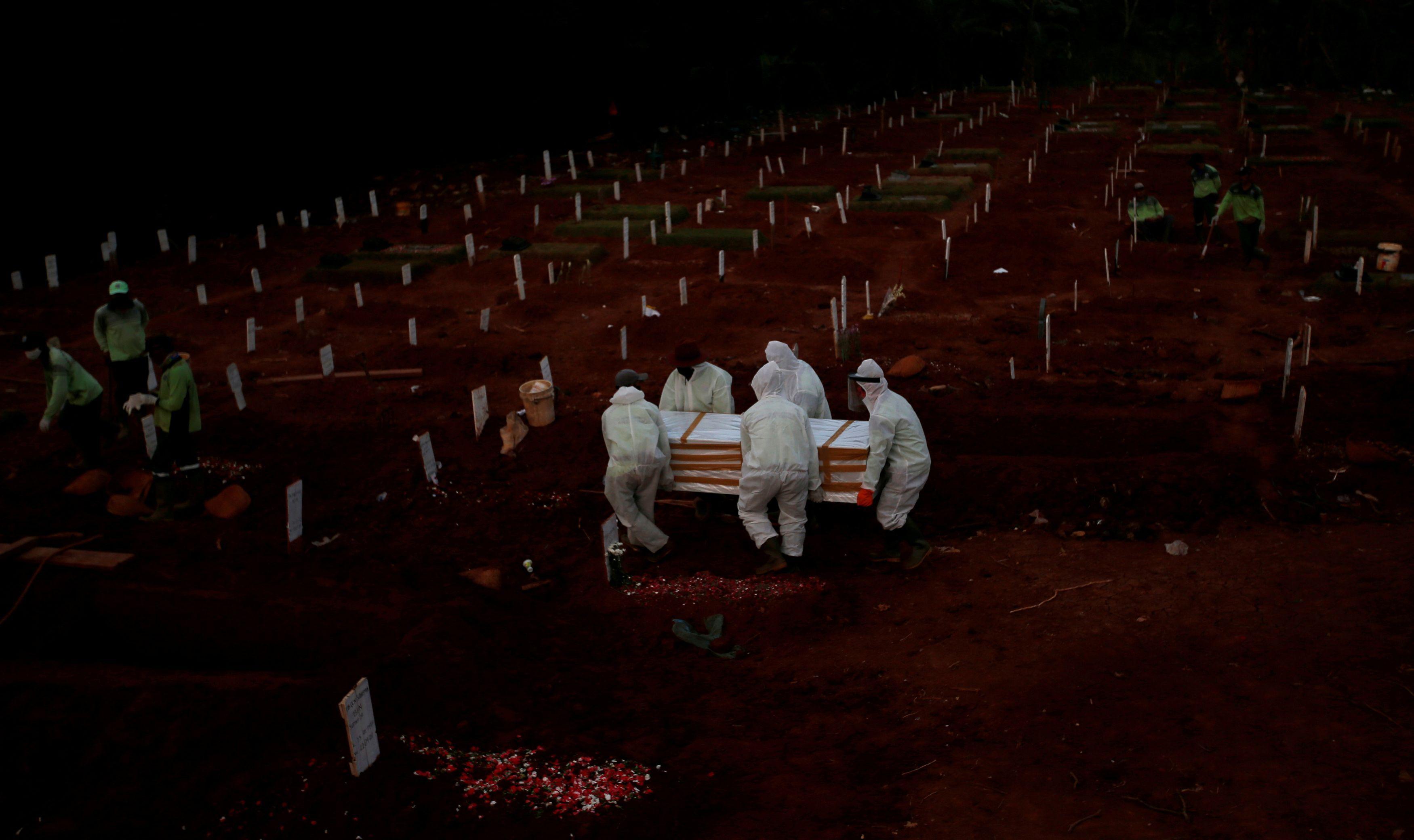 インドネシアのジャカルタで、墓地に埋葬される新型コロナ感染症の犠牲者=22日(ロイター=共同)