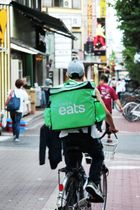 関西でもサービスを開始したウーバーイーツ。黄緑色の宅配用バッグを見る機会も増えた=大阪市淀川区西中島1、西中島南方駅