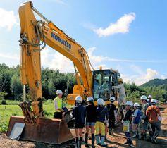 築堤工事で使われるクレーン車に乗り、操作を教わる児童たち(京都府福知山市大江町北有路)