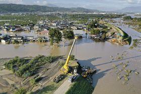 台風19号で増水し、千曲川(右側)の堤防が決壊した現場。住宅地に濁流が流れ込んだ=13日午後、長野市穂保(小型無人機から)