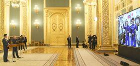 大型モニターに映る宇宙飛行士の金井宣茂さん(右)とアントン・シュカプレロフさんと交信し、手を振る安倍首相(左端)とロシアのプーチン大統領=26日、モスクワのクレムリン(共同)