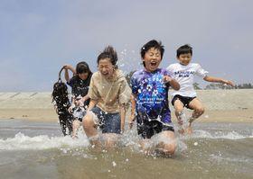 9年ぶりに海開きした宮城県気仙沼市の小泉海水浴場で、海に駆け込む地元の小学生たち=20日午前