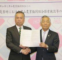 協定を結び握手を交わす谷口市長(左)と内田組合長