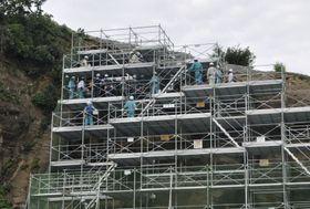 中国電力島根原発の防波壁西端にある山の地形や地層を調べる原子力規制委の委員ら=20日、松江市