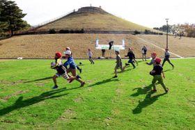 """移植された""""W杯の芝""""の上でラグビーを楽しむ児童ら=横浜市都筑区の川和富士公園"""