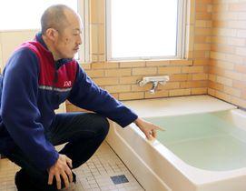 給水停止に備え、水をためた風呂を示す上村聡さん=17日、岩手県雫石町