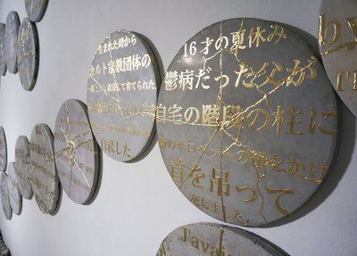 芸大を修了後、部屋にひきこもった渡辺篤は「アートは人の心に寄り添うことができる」と考え、多くの人から寄せられた文章を円形板に刻んだ(プロジェクト「あなたの傷を教えて下さい。」より)(敬称略)