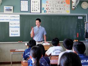 北京五輪で獲得した銅メダルを見せながら説明する宮下純一さん=久喜市立栗橋西中学校