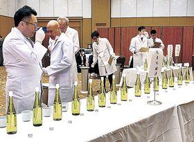新酒を口に含み、味や香りを確かめる審査員=26日午前9時半、金沢市内のホテル