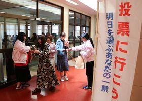 投票を呼び掛けるチラシなどを配る学生たち=長崎市、長崎純心大