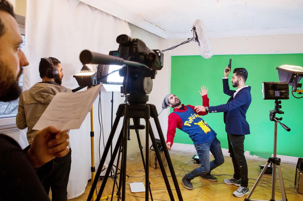 風刺動画の撮影で、銃で撃たれるIS戦闘員の役を演じるバキール(右から2人目)。「シリアでは日常があまりに悲劇的だから、喜劇の方が人々の記憶に残るんだ」と監督のヘラーリ(左端)は言う=トルコ・イスタンブール(撮影・ニコール・タング)