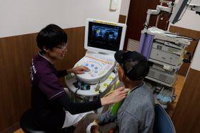 【頸動脈のエコー検査を体験する来場者(右)=木曽岬町和富の「もりえい総合ヒューマンケアステーション」で】