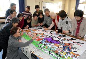 鈴が峰公民館で横断幕を作る絵手紙サークルのメンバー
