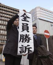 日本郵便の待遇格差訴訟の控訴審判決で、「全員勝訴」の紙を掲げる弁護士=24日午後、大阪高裁前