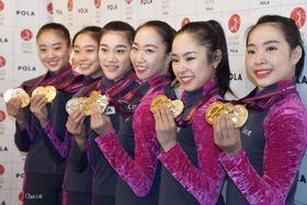 新体操の世界選手権から帰国し、獲得したメダルを手にする団体の杉本早裕吏主将(右から3人目)ら=24日、成田空港