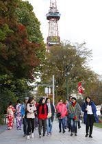 札幌市のテレビ塔前を歩く観光客=17日