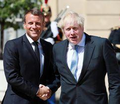 22日、パリで握手を交わすフランスのマクロン大統領(左)と英国のジョンソン首相(ゲッティ=共同)