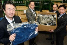 発展途上国に届ける衣類をクリーニングした石井大社長(左)=神戸市灘区琵琶町3