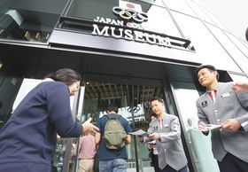 日本オリンピックミュージアムがオープンし、ライフル射撃の松田知幸選手(右)と秋山輝吉選手が迎える中、入館する人たち=14日午前10時2分、東京都新宿区で(中西祥子撮影)