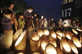阪神大震災から23年を迎え、竹灯籠が並べられた追悼会場で黙とうする人たち=17日午後5時46分、神戸市中央区の東遊園地