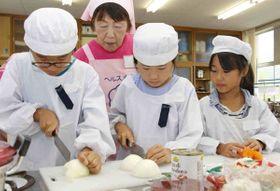 山本会長(左から2人目)に教わりながら調理に挑戦する児童=丸亀市飯野町、飯野小