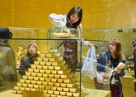 ハウステンボスにオープンした「黄金の館」で、重さ約12キロの金塊に触れる来場者=16日午後、長崎県佐世保市