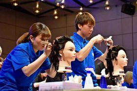 細いくしを使ってマネキンの髪に次々にロッドを巻く出場者=16日午前、宮崎市・MRTmicc
