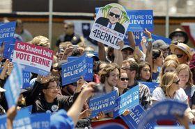 「学生の借金を終わらせろ」などのプラカードを掲げ民主党のサンダース上院議員を支持する人々=2016年5月26日、カリフォルニア州(AP=共同)